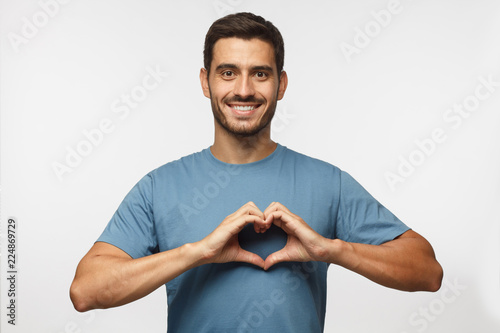 Photo Young smiling handsome smiling male in blue t-shirt showing heart sign isolated
