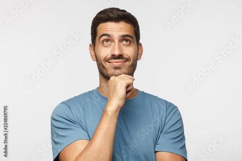 Young man in blue t-shirt with dreamy cheerful expression, thinking, looking up, Canvas