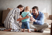 Young Mother And Father Is Having Fun Playing With A Baby At Home.