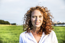 Portrait Of Freckled Young Woman With Curly Red Hair