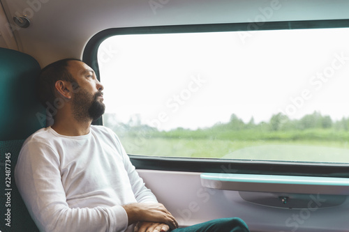 Portrait of a pensieve man on train looking outside of the window, traveling