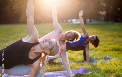 Fotografia  Yoga at park, group of mixed age women doing pose while sunset