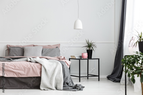 Fotografie, Obraz  Warm blankets and gray pillows on a cozy double bed with dirty pink sheets by an