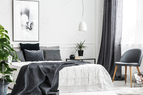 Photo  Modern, gray chair with wooden legs by a window of a bright bedroom interior wit