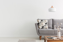 Flowers On Wooden Table And Grey Settee In White Living Room Interior With Copy Space. Real Photo