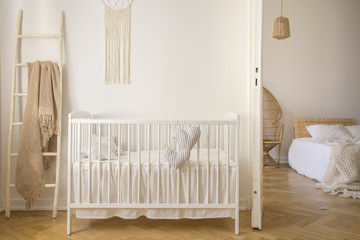 Obraz na Plexi Wooden crib with cushions standing in real photo of white kid room interior with blanket on ladder and macrame on the wall