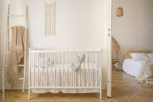 Fotografering Wooden crib with cushions standing in real photo of white kid room interior with