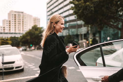 Valokuva Smiling businesswoman getting into a taxi