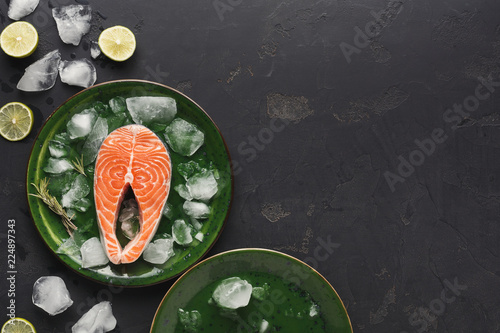 Fresh salmon with ice on dark background