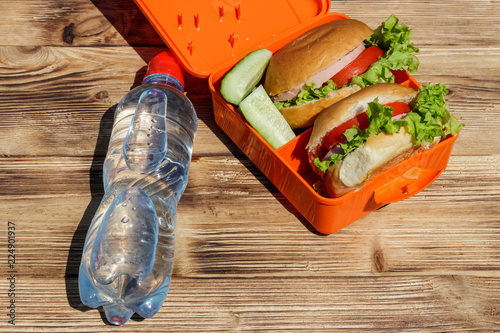 In de dag Assortiment Bottle of water and school lunch box with two homemade burgers and fresh cucumbers on wooden table