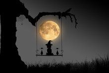 The Witch Child And Two Cat Sitting On The Wooden Swing In The Night Of The Full Moon On Halloween Concept.