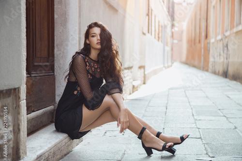 Fototapeta premium Podróżować dziewczyny turystycznej na wakacje pozowanie na ulicy miasta. Atrakcyjna młoda romantyczna pasja kobieta siedzi na chodniku przed pięknym widokiem na weneckiej cichej ulicy w Wenecji, Włochy. Wspaniała mieszana rasa