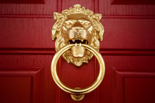 Close-Up Of Lion Head With Ring In Mouth Door Knocker On Painted Wooden Red Door. Traditional English Brass Door Knocker.