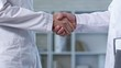 Close up shot of two unrecognizable people in lab coats standing in office and shaking hands after reaching agreement