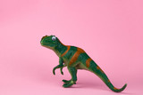 funny green dinosaur toy on pastel pink background