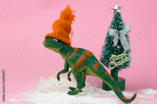 Photo  funny green dinosaur toy in littleorange knitted  hat  near little christmas tre