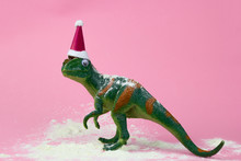 Funny Green Dinosaur Toy In Little Santa Claus Hat  And Snow On Pastel Pink Background
