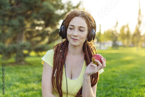 Modern woman with dreadlocks listening to music with her headphones in autumn Sunny Park Canvas Print