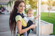 Young happy mom with cute baby son in ergo backpack walking in the Park. Concept of modern mother