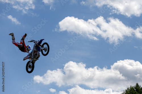 Sports, extreme, speed, adrenaline concept. Stylish biker jumping on his motorcycle and flying in the sky among the clouds.