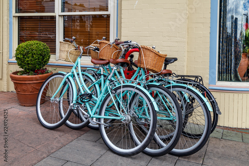 In de dag Fiets Blue bicycles with baskets against the wall.