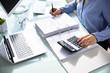 Leinwandbild Motiv Businesswoman's Hand Calculating Bill In Office