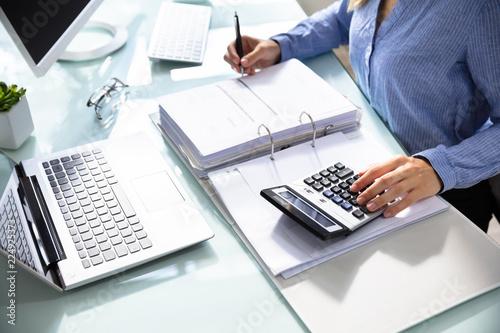 Obraz Businesswoman's Hand Calculating Bill In Office - fototapety do salonu