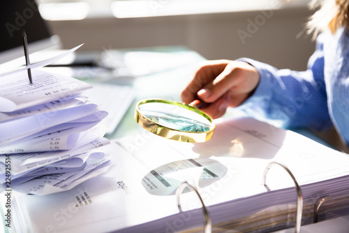 Foto  Businesswoman Checking Invoice With Magnifying Glass