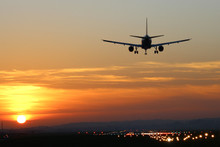 Plane Landing At Runway On The Background Of Sunset