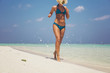 Woman taking morning running at the beach