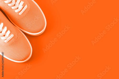Fotografia  Bright orange sneakers on an orange background.