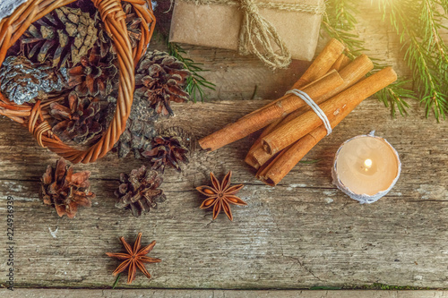 Tuinposter Kruiderij Christmas New Year composition with gift box fir branch basket pine cones candle on old shabby rustic wooden background. Xmas holiday december decoration to Russian tradition. Flat lay, copy space