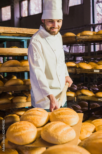 Staande foto Bakkerij Baker. A young handsome bakery worker on the background of bread, takes bread from a stove with a wooden shovel. Industrial production of bakery products. a man in the baker's special clothing. Bakery
