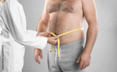 Fotografia, Obraz  Doctor measuring man's waist on grey background, closeup