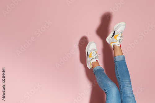 Woman in stylish sneakers near color wall, closeup Fototapeta