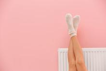 Woman Warming Legs On Heating ...