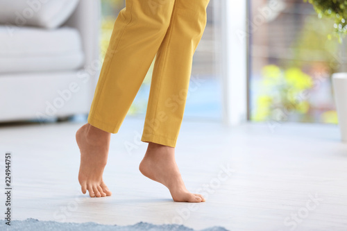 Photo Woman walking barefoot at home, space for text. Floor heating
