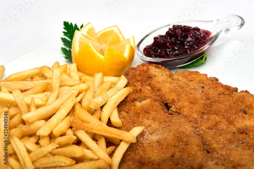 Cuadros en Lienzo Italian food, Milanese schnitzel with fries  served on white plate, isolated on