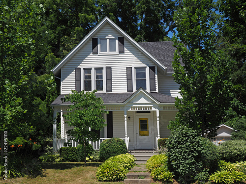 White clapboard house with gable surrounded by trees Canvas Print