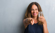 Middle age hispanic woman drinking glass of water pointing with finger to the camera and to you, hand sign, positive and confident gesture from the front