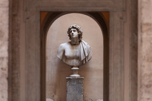 Sculpture Of A Male Bust In A Small Courtyard