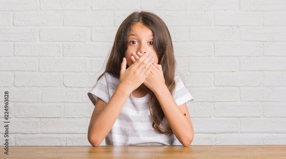Fototapeta Young hispanic kid sitting on the table at home shocked covering mouth with hands for mistake. Secret concept.
