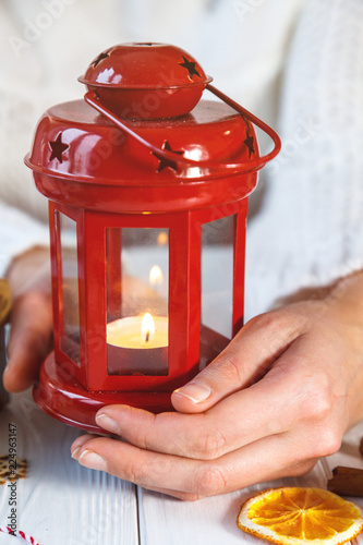 Photo  Woman in winter, white cozy sweater holding a red lantern with candle on white table