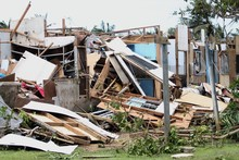 The Damaged Remains Of Wooden Houses After A Typhoon Hit A Tropical Island, With Missing Roofs And Devastation All Around