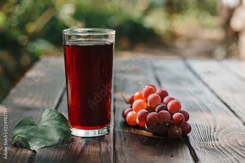Bunch of red grapes and glass of grape juice on wooden garden table, refreshing organic antioxidant beverage