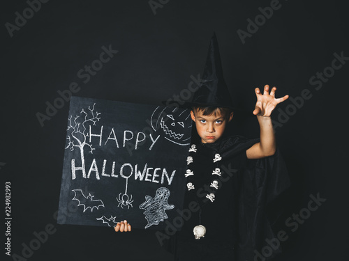 young boy dressed as a magician is holding happy halloween chalkboard in front of black background