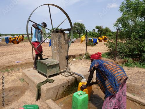 Obraz donna africana raccoglie l'acqua al pozzo  - fototapety do salonu