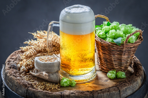 Tuinposter Bier / Cider Gold pint of beer on wooden barrel