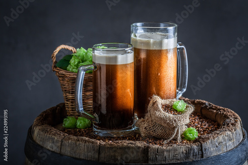 Staande foto Bier / Cider Cold dark beer on old wooden barrel