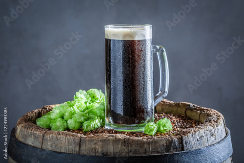 Staande foto Bier / Cider Cold pint of dark beer on old barrel